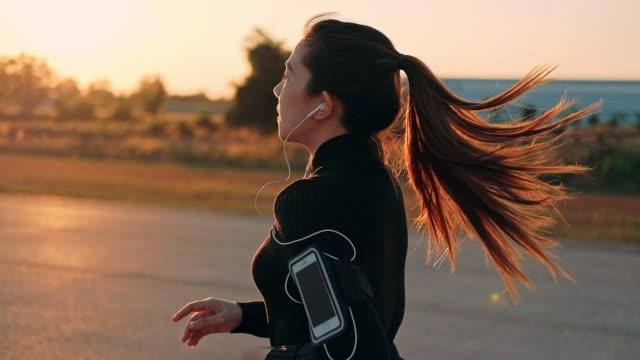 日没時間 (スローモーション) で実行されているイヤホンと女性 - アドレナリン点の映像素材/bロール