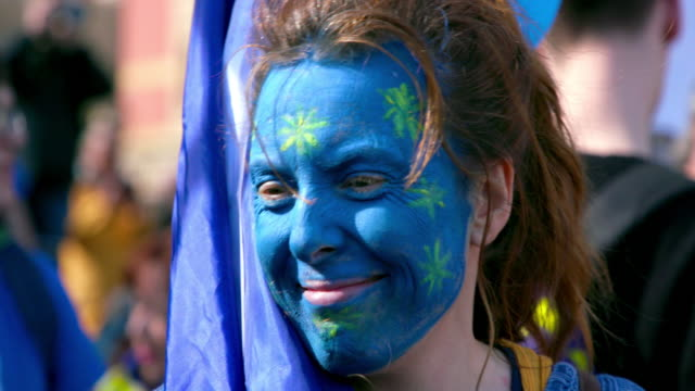 woman with european union flag face paint; parliament square, london - britisches parlament stock-videos und b-roll-filmmaterial