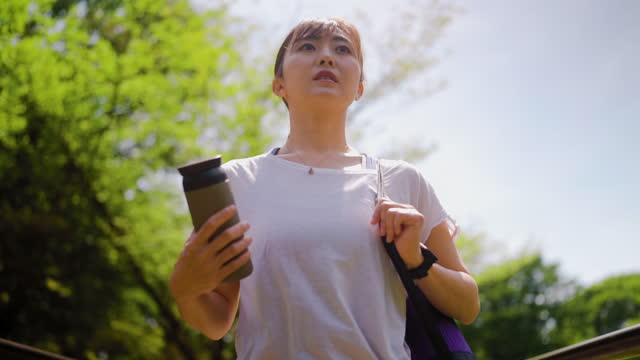 vídeos y material grabado en eventos de stock de mujer con estera de ejercicios caminando en la naturaleza - una mujer de mediana edad solamente