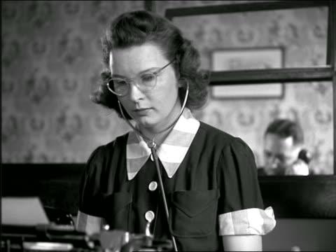vídeos y material grabado en eventos de stock de b/w 1937 woman with eyeglasses + headphones typing on typewriter - secretaria