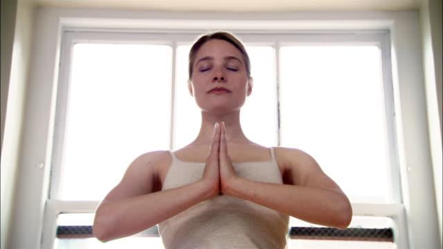 Woman with eyes closed and hands in prayer position in yoga studio / zoom in to woman's face