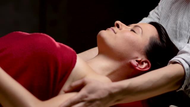 vidéos et rushes de femme avec les yeux fermés appréciant le massage de tête de masseuse dans le salon de spa de luxe - se faire dorloter