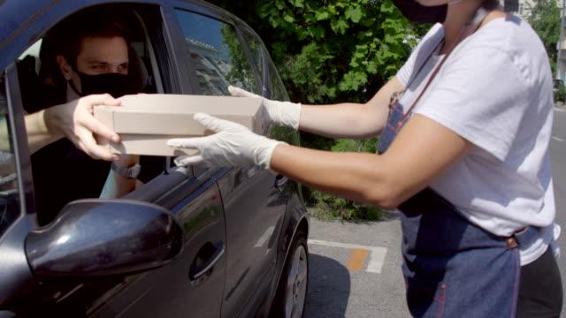 vidéos et rushes de femme avec le masque de visage et les gants prenant des boîtes de pizza au client dans la voiture - trottoir