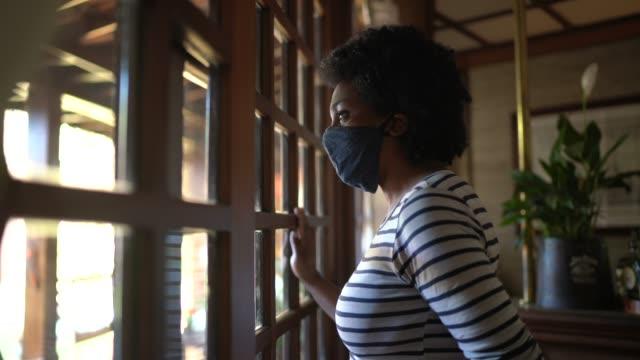 frau mit gesichtsmaske schaut durch das fenster und denkt zu hause - african american ethnicity stock-videos und b-roll-filmmaterial