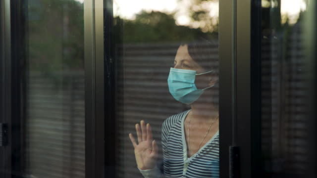 woman with face mask looking through window - obscured face stock videos & royalty-free footage