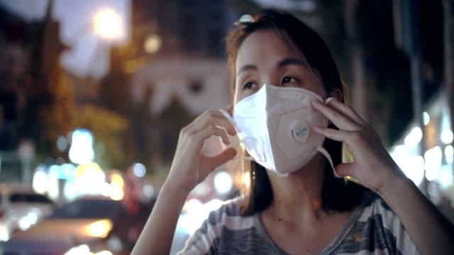 夜の大気汚染から顔マスク保護を持つ女性 - 花粉症点の映像素材/bロール