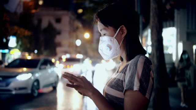 Woman with face mask protection from air pollution using smart phone at night