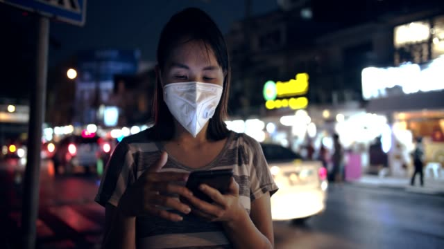 woman with face mask protection from air pollution using smart phone at night - smog stock videos & royalty-free footage