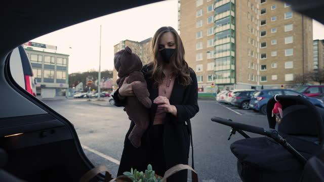 kvinna med ansiktsmask sätta matkassar i bilen - bära bildbanksvideor och videomaterial från bakom kulisserna