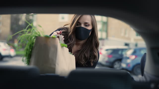 woman with face mask putting grocery bags in the car - car interior stock videos & royalty-free footage
