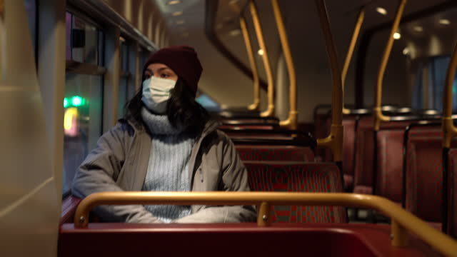 woman with face mask traveling by bus in london - winter stock videos & royalty-free footage