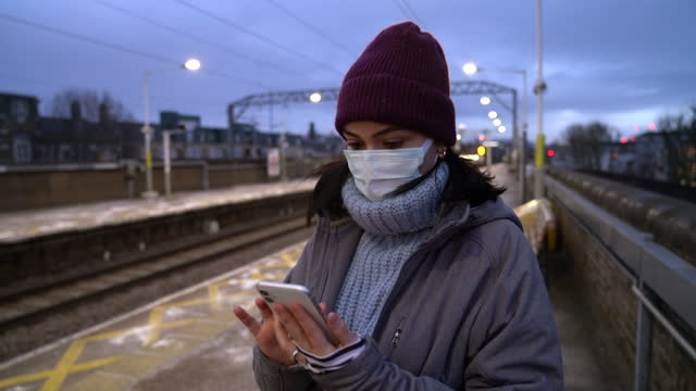 woman with face mask using mobile phone in the train station - cinematography stock videos & royalty-free footage