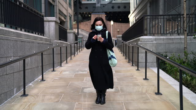 woman with face mask using smart phone - cinematography stock videos & royalty-free footage