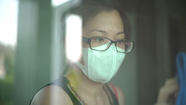 cu woman with face mask using spraying alcohol and cleaning the window at home - collaboratore domestico video stock e b–roll