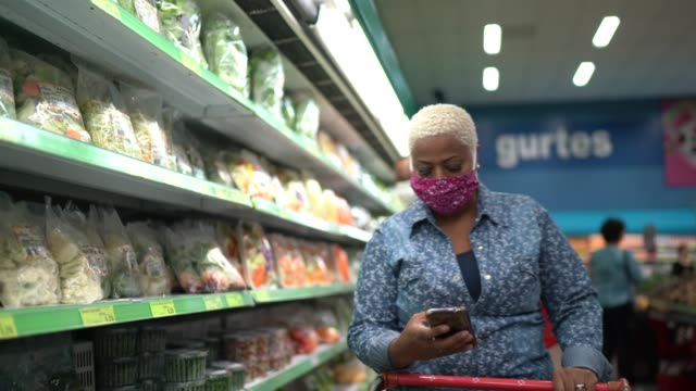 vídeos de stock e filmes b-roll de woman with face mask walking and using mobile at supermarket - mercadoria