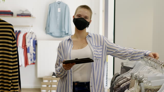 woman with face mask working in a clothing store - boutique stock videos & royalty-free footage