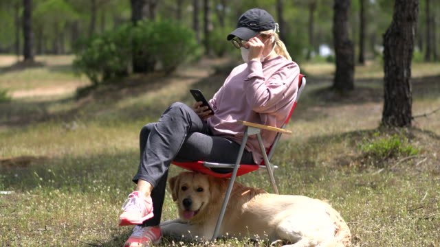 woman with face protective mask sitting with her dog in forest - camping stock videos & royalty-free footage