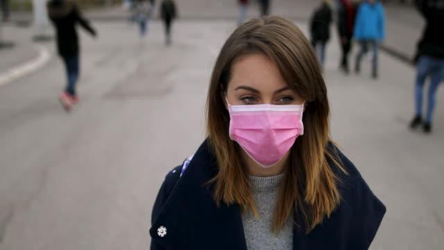frau mit gesichtsschutzmaske - mundschutz stock-videos und b-roll-filmmaterial
