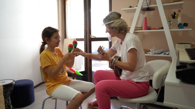 woman with face shield and girl making music together during music therapy - invisible disability stock videos & royalty-free footage