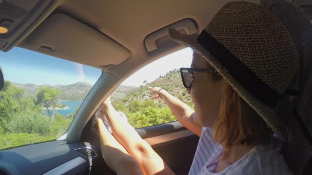 vídeos de stock, filmes e b-roll de ms woman com os pés para fora da janela, aproveitando a viagem de verão no carro - de pé para cima