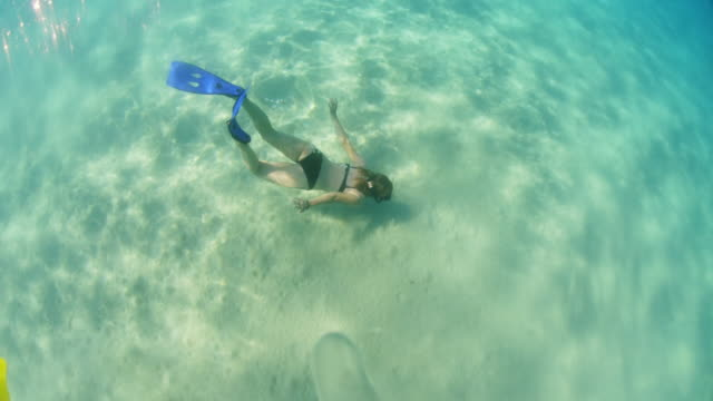 MS Woman with flippers diving underwater into sunny turquoise blue ocean