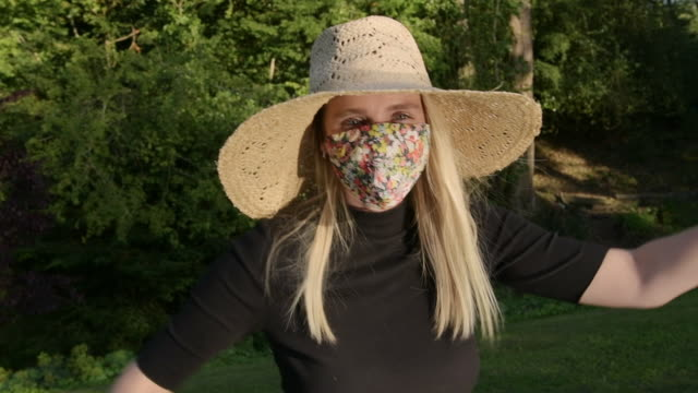 woman with floral face mask making waves playfully with arms being silly on sunny day in park - sunny video stock e b–roll