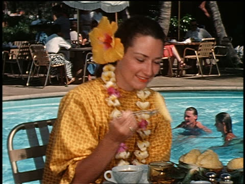 1960 woman with flower in hair + lei eating pineapple next to swimming pool / offers to someone / hi - pineapple stock videos & royalty-free footage