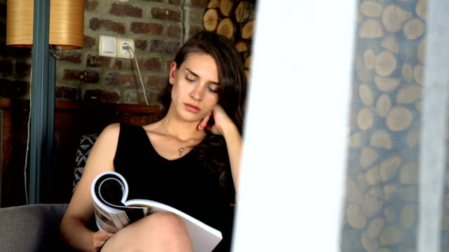 woman with formal clothes sitting and reading magazine in porch - magazine publication stock videos & royalty-free footage