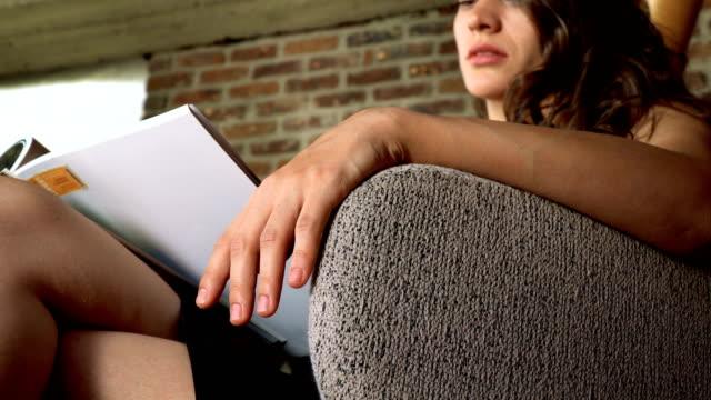 vídeos y material grabado en eventos de stock de mujer con ropa formal sentada y revista de lectura - magazine