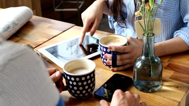 Frau mit Freund mit Digital-Tablette im Cafe