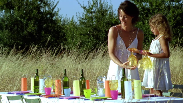 ms, woman with girl (6-7) preparing dinner table in meadow, saint ferme, gironde, france - tre quarti video stock e b–roll