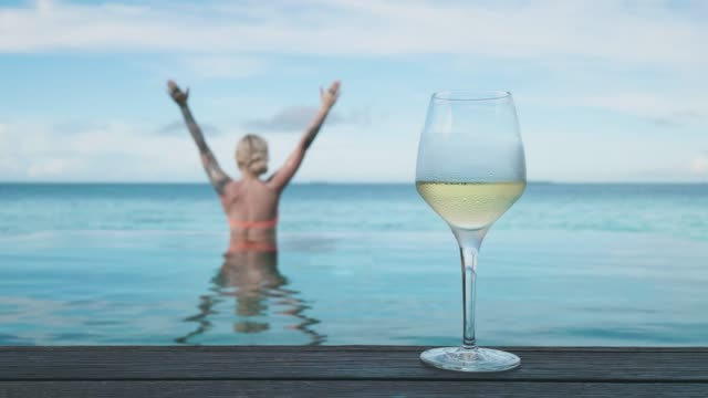 vídeos de stock e filmes b-roll de woman with glass of wine by the pool - cinemagraph - amimar
