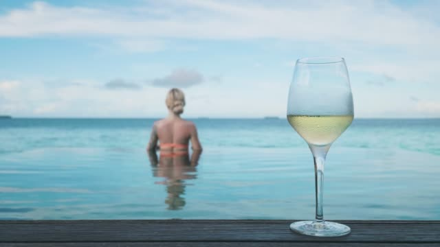 woman with glass of wine by the pool - cinemagraph - white wine stock videos & royalty-free footage