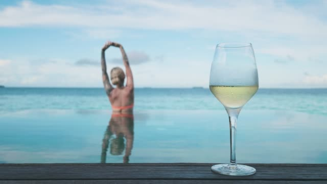woman with glass of wine by the pool - cinemagraph - infinity pool stock videos & royalty-free footage