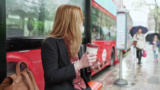 woman with glasses sitting at a bus stop drinking coffee - commuter stock videos & royalty-free footage