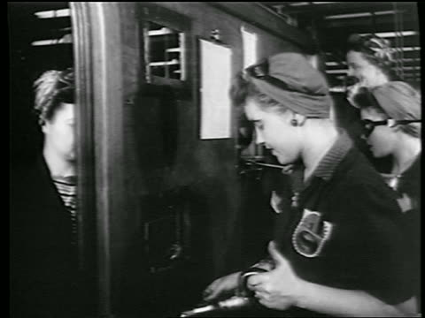 stockvideo's en b-roll-footage met b/w 1944 woman with goggles kerchief on head riveting in defense plant / other women in background / ww ii - first line of defense filmtitel