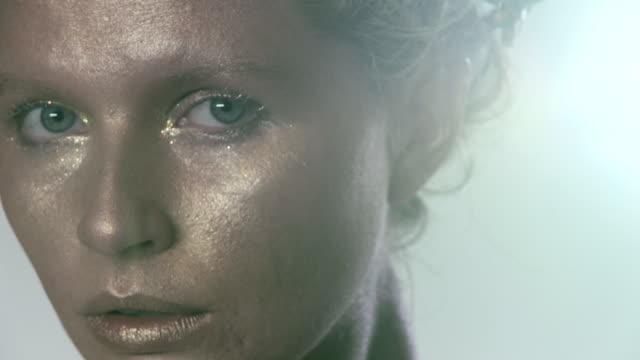 vídeos y material grabado en eventos de stock de woman with golden make up on face - foco difuso
