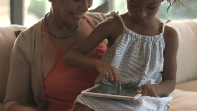 woman with granddaughter using tablet pc - device screen stock videos & royalty-free footage