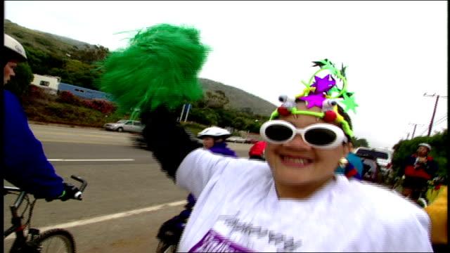 woman with green pom pom cheering on bike riders at aids benefit ride malibu california - pom pom stock videos & royalty-free footage