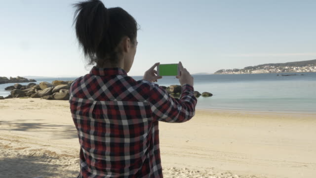 woman with green screened smart phone at the beach - brown hair stock videos & royalty-free footage