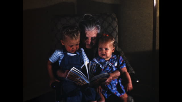 "woman with grey hair sitting on the sofa, two kids on her lap reading a book; title card with the words ""ready to go""; toddler girl in blue dress... - book stock videos & royalty-free footage"