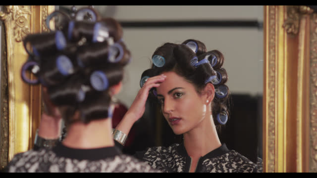 A woman with hair in rollers, looks in a mirror