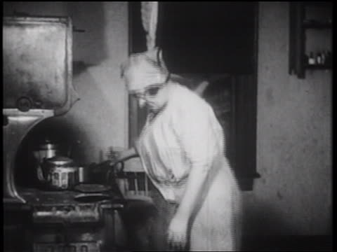 B/W 1939 woman with handkerchief on head stoking fire of coal-burning stove / documentary