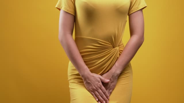 woman with hands holding over isolated yellow background - menstruation stock videos & royalty-free footage