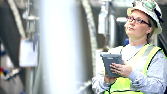 woman with hardhat and safety vest working in factory - storage tank stock videos & royalty-free footage