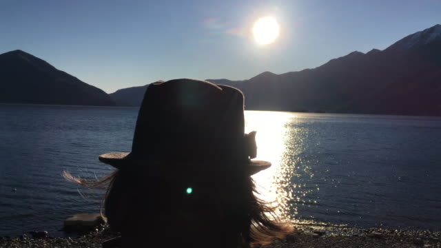 woman with hat and enjoy the panoramic view over alpine lake - オーバーコート点の映像素材/bロール