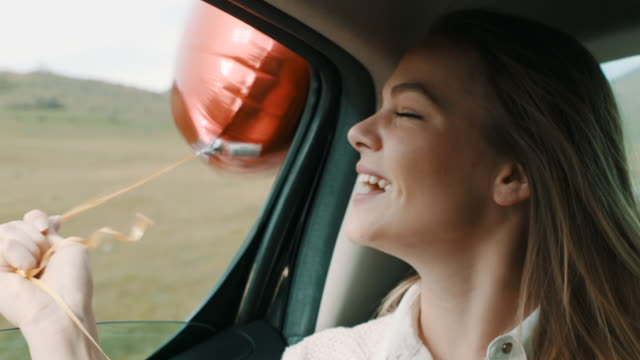 woman with hat on her head having fun on back seat of the car with air balloon - car interior stock videos & royalty-free footage