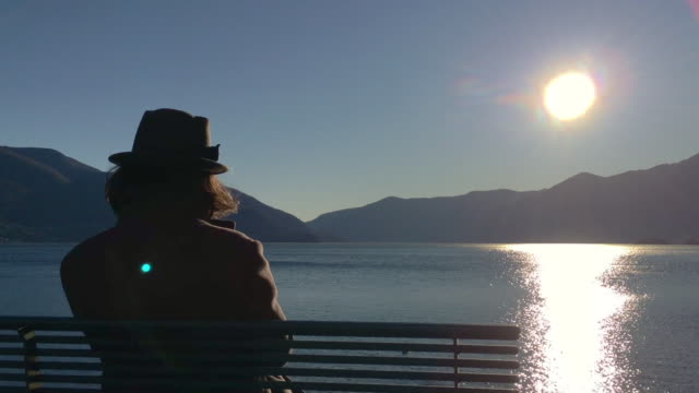 vidéos et rushes de woman with hat sitting on a bench and enjoy the sun over alpine lake with mountain - seulement des femmes d'âge mûr