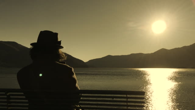 woman with hat sitting on a bench and enjoy the sun reflection over alpine lake with mountain in sepia toned - sepia stock videos & royalty-free footage