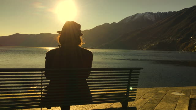 woman with hat sitting on a bench and enjoy the view over alpine lake with mountain and sunlight - オーバーコート点の映像素材/bロール